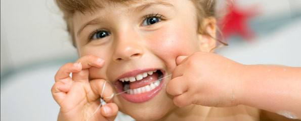Child flossing their baby teeth.